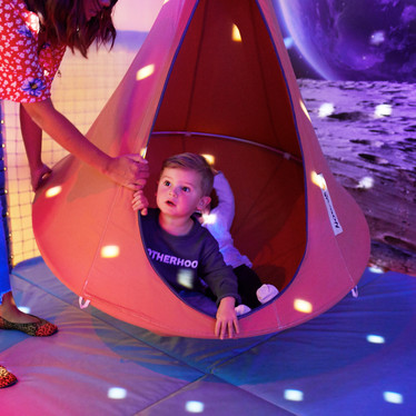Swing seat on the moon in the space themed sensory room at Head Over Heels Play Chorlton