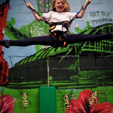 Girl enjoying energetic play on the bungee trampolines at Head Over Heels Wilmslow