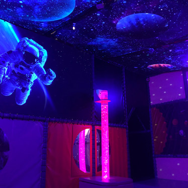 Glowing spaceman and galaxies in the sensory room at Head Over Heels Play Chorlton