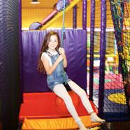 Girl enjoying energetic play on the swing at Head Over Heels Wilmslow
