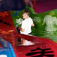 Boy enjoying energetic play on the slide at Head Over Heels Wilmslow