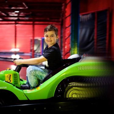 Boy on green electric racing car at Head Over Heels Wilmslow