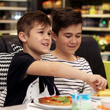 Boys eating children's pizza in family restaurant at Head Over Heels Wilmslow