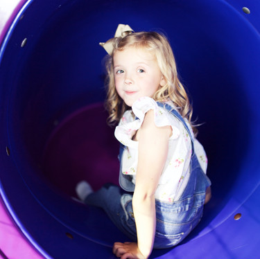 Girl at the top of the tunnel slide at Head Over Heels Wilmslow