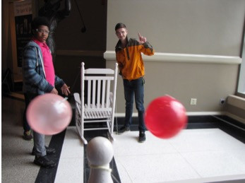 Caleb (right) races a balloon on a string with a participant