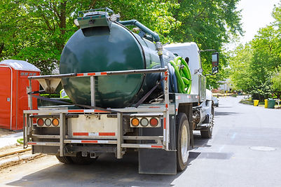 Vacuum waste truck on the cleaning process portable bio toilet cabins at the construction.