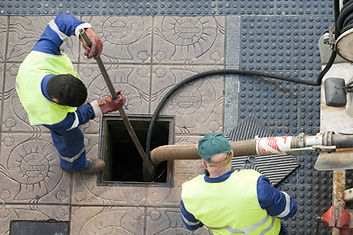 utilities workers moves the manhole cove