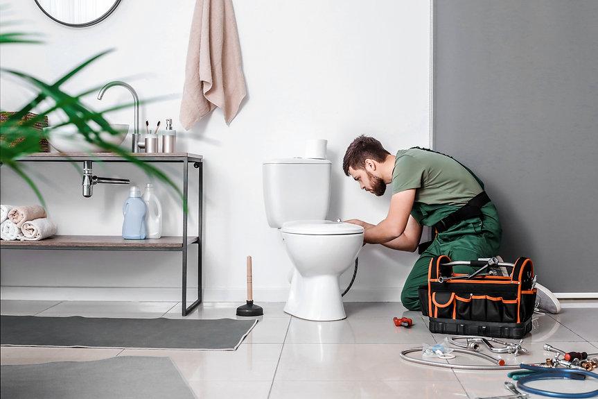 Plumber installing toilet bowl in bathro