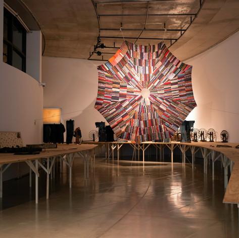 """作品《閃光と落下傘》遠藤薫 、2020年提供:青森公立大学 国際芸術センター青森(ACAC) Art works: """"Flash and Parachute""""  ENDO Kaori, 2020, old cloth  Courtesy of: Aomori Contemporary Art Centre (ACAC), Aomori Public University  グループ展『いのちの裂け目ー布が描き出す近代、青森から』展 (青森公立大 国際芸術センター青森)、2020 group show """"The Beginning of Life/ Art: Cloth Weaves Our Times, from Aomori"""" (Aomori Contemporary Art Centre, Aomori Public University)、2020  みんなが爆弾なんかつくらないで きれいな花火ばかりをつくっていたら きっと戦争なんか起きなかったんだな―山下清 生活に根差した工芸の本質を現代美術的な視座から探るべく、テキスタイルに複雑な社会的事実が織り込まれていると考え、布を集め使用と修復の行為を繰り返す、工芸/美術作家の遠藤薫。彼女は、第二次世界大戦の徴兵を逃れるため放浪をはじめたとされる画家・山下清(1922-1971年)の言葉に触発され、戦争と花火に関するインスタレーションを制作しました。 山下の代表作である貼り絵に《長岡の花火》(1950年)がありますが、長岡の花火で打ち上げられる「白菊」は、第二次世界大戦終戦間近の1945年8月1日に起きた長岡空襲の被害者を慰霊するための花火です。ちなみにここ青森も長岡の4日前に大空襲を受け、大勢の人が亡くなりました。夏の風物詩である花火。その形色とりどりの閃光と雷薬による爆発音は、時に見る者を感動させ、時には空襲など戦争を連想させるものとなり得るでしょう。 遠藤は今回、もう着られなくなった着物を、青森を含む全国各地から譲り受け、裂き、津軽裂織の技術を学んで、落下傘(パラシュート)を織りあげました。飛行機からの脱出手段として、人命を守るために実用化された落下傘。その後、敵地を空から攻める兵士輸送の方法として落下傘降下は発達しました。長い時間のかかる織りの作業は、数多の先人たちが指摘するように、どこか祈りに似ています。そして、遠藤が青森市教育委員会蔵の民俗資料から選び出したのは、多くの人々の手を経て傷んでいる、もしくは壊れている農機具と、大切にまとわれてその時間の分だけ変化した着物の数々です。 ある日偶然、青森市立長島小学校の卒業生に教えられ、遠藤は山下清が描いたと伝えられる花火のペン画と出会うことになりました。あらゆる事物の移動によって、時と場所を超えて同じようなことが起こること。すべてが無関係ではないこと。戦争は決して終わったことではないこと。布を作り使い、なおす。そのような生活のなかの行為の延長線上で、遠藤は誰かの生の続きを生きようとしているかのようでもあります。 If no one made bombs and made only beautiful fireworks instead, wars would never have happened. - Kiyoshi Yamashita      Considering that complex social facts are woven in textiles, the textile/visual artist ENDO Kaori collects textiles and repeatedly uses and restores them, in her search for the essence of crafts, rooted in people's life, through a contemporary art perspective. Inspired by the remark made by the painter Kiyoshi Yamashita (1922-1971), who is said to have started wandering about to escape from the draft   during the Second World War, she created an installation themed around war and fireworks.          While there is a masterpiece of collage by Yamashita, called Nagaoka Fireworks (1950), one t"""