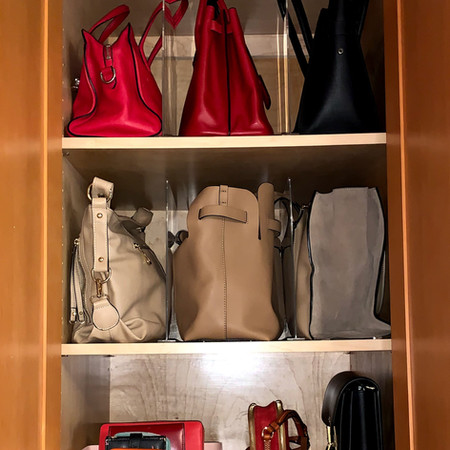 Purses neatly organized on cupboard shelves with acrylic dividers.