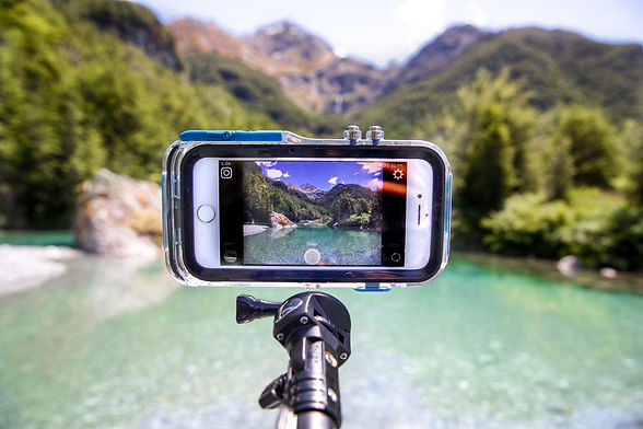 ProShotCase with iPhone inside mounted on an extendable pole mount taking picture of New Zealand lake and mountains landscape