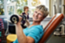 Happy senior female with dumbbells in gy