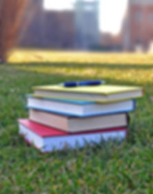 Stack of college books and a pen in a grassy campus quad