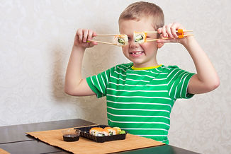 Child eat sushi rolls at home..jpg