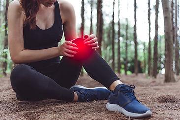 Sport woman injury at knee during joggin