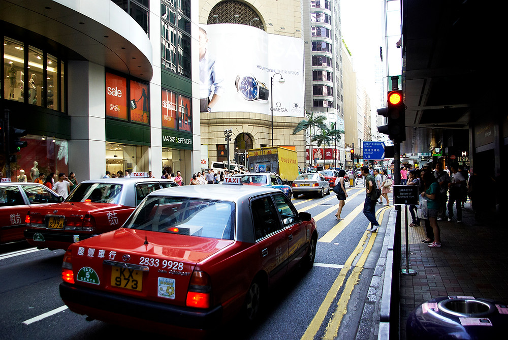 Hong Kong taxi at red traffic light in busy Central district