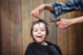 A little boy is trimmed in the hairdress