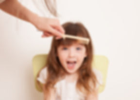 Woman's hand combing her bangs for a lit