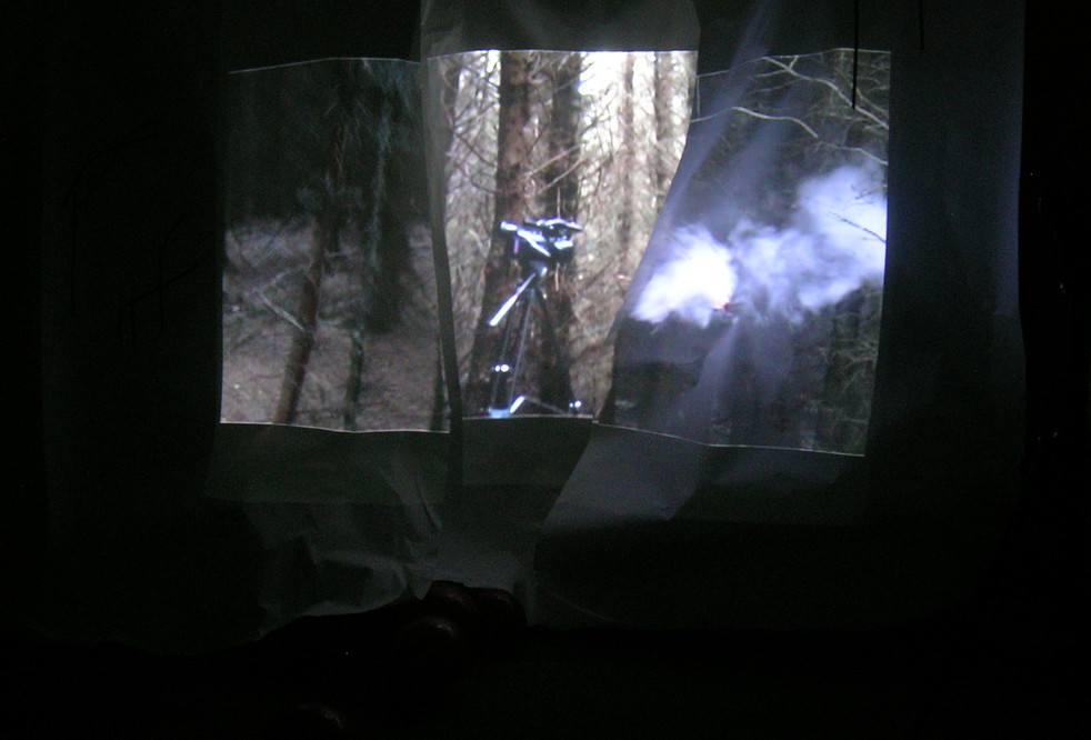Forest, 2011 projection view  Alchemy Film & moving Image Festival Hawick, Scottish Borders  This commissioned installation piece was filmed and devised for Alchemy during a residency at Heriot Toun Studio in the summer prior to the festival.  10 days were spent filming and experimenting, alone in various tracts of plantation woodland, where the artist created various  'apparitions'; using smoke, red balloons and mirrors; These materials, used in previous artworks, represent here the breath and the self; fleeting mindfulness, but also the heightened senses of moments of fear; when one feels there could be another observer in that deserted place.  The installation invites the viewer into a visceral sense of that aloneness and self consciousness – being the watcher watching the watcher. The majority of the 5 minute split screen projection features footage taken of the video camera itself on a tripod in the still, silent forest; representing both the artist and the viewer in the space. Meanwhile, other footage is then mapped onto a tumbling, crumpled paper screen, from beneath which a cluster of the same red balloons seem to be escaping  The remaining walls, and parts of the carpeted floor, are adorned with a simplified, almost codified forest motif, created from black electrical tape – representing the relatively monochrome, lifeless and noiseless environment of this type of pine forest at ground level.  The video is silent, with the intention of demanding a more raw encounter. Where an atmospheric sound-scape would provide an easier path for the viewer to the intended emotional response, perhaps the silence presents more directly that sense of unease and exposure.