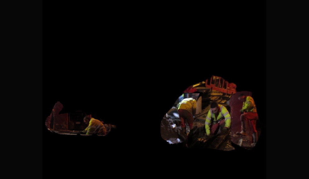 Road Works, detail;  Sandbags 1   Hidden Door Festival 2015,  Edinburgh  This installation at Hidden Door Festival in 2015, presented footage of road workers digging into the ground, late at night, mapped onto a still life of sandbags slumped on the floor of the gallery The intention of the work is duplicitous: both cynical and celebratory Laughing, and loving being observed and appreciated, the workmen represent a homage to camaraderie, and grafting for a living; surviving; learning, persevering.  Meanwhile the sand bags become totemic, shamanistic; portals to an unreal world of mysterious work.  With four workmen endlessly digging their way out of the sand bags, the piece simultaneously offers a sense of the bizarre. With a play on the idea of 'digging holes' ('if you find yourself in a hole, stop digging'), it takes a humorous look at the never ending process of maintaining and improving services and roads as a metaphor for life's inherent struggle; and the futility or foolishness therein. This piece was made with the permission and input of the workers.