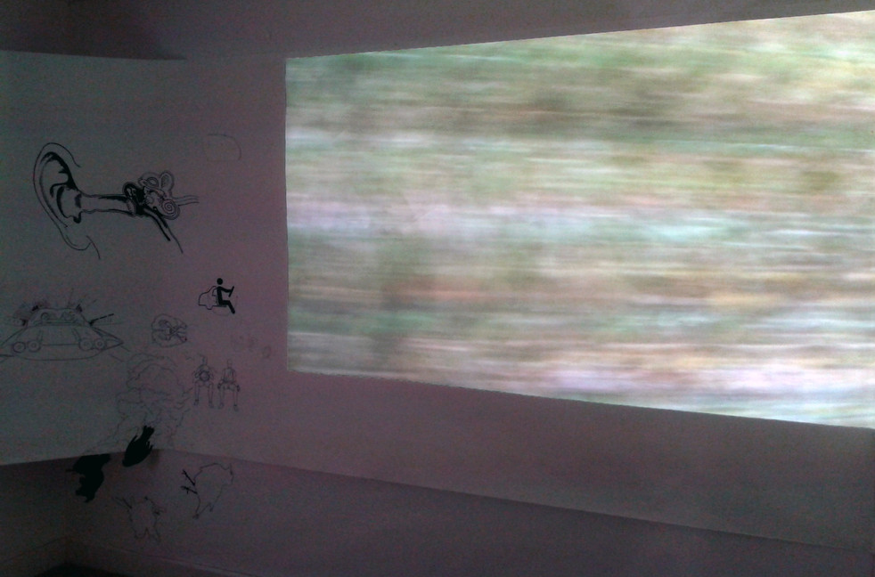 Drive, 2012 installation view  Alchemy Film & Moving Image Festival  Hawick, Scottish Borders  This film was developed as an installation piece including 35mm slide projections, and drawings.  The piece set out to express the intensity of feeling that can be experienced on and about certain journeys; familiar, or one-time journeys, as they reside in memory.   In this case, the particular focus was on a coastal journey from South West Wales to North Wales. I wanted to explore the way that a sense of one's geography is heightened by proximity to an edge or boarder - the proprioception of landscape, as well as the way memory functions to create and consolidate meaning, attaching powerful emotions to visual and sensory cues, so that a journey through landscape can provide or become a ritual of pilgrimage or transition. The layering within the video of racing water and wind swept grass as well as evocative home movie style clips, through the motif of a rear-view wing mirror plays with both the idea of leaving and the physicality of driving; the unnatural nature of speed and the continual displacement of air, rushing to fill the space/moment we left behind.