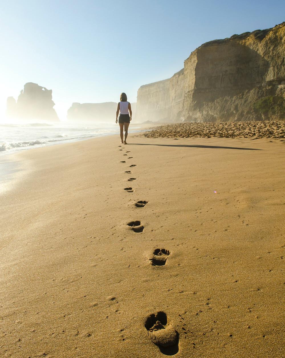 Girl walking on a beach leaving foot prints