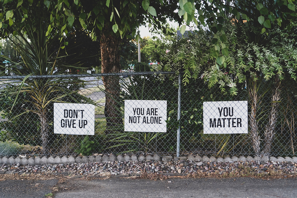"""Signs saying """"you are not alone"""", """"You matter"""", and  """"Dont Give up"""""""