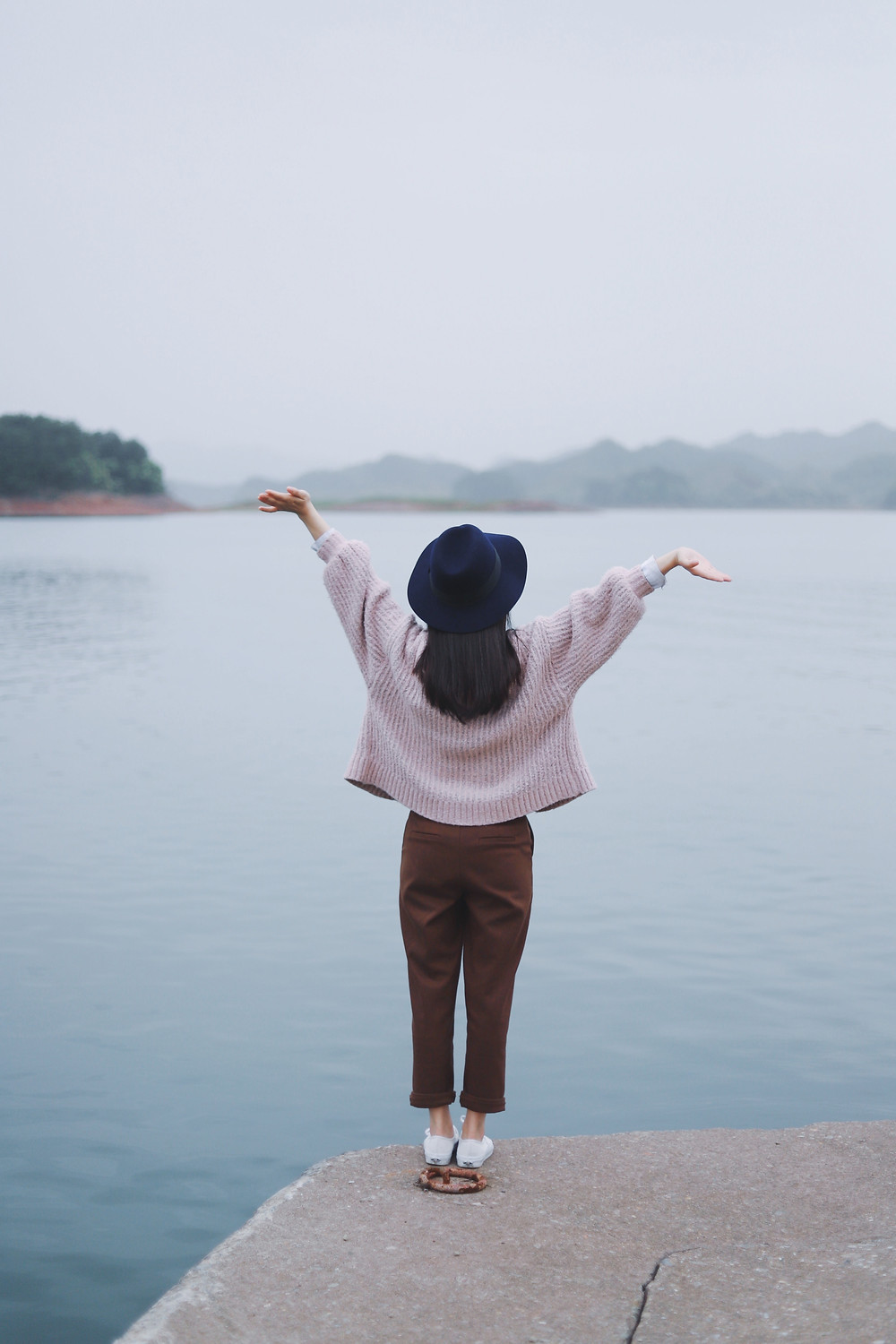 Girl looking out over water with hands up