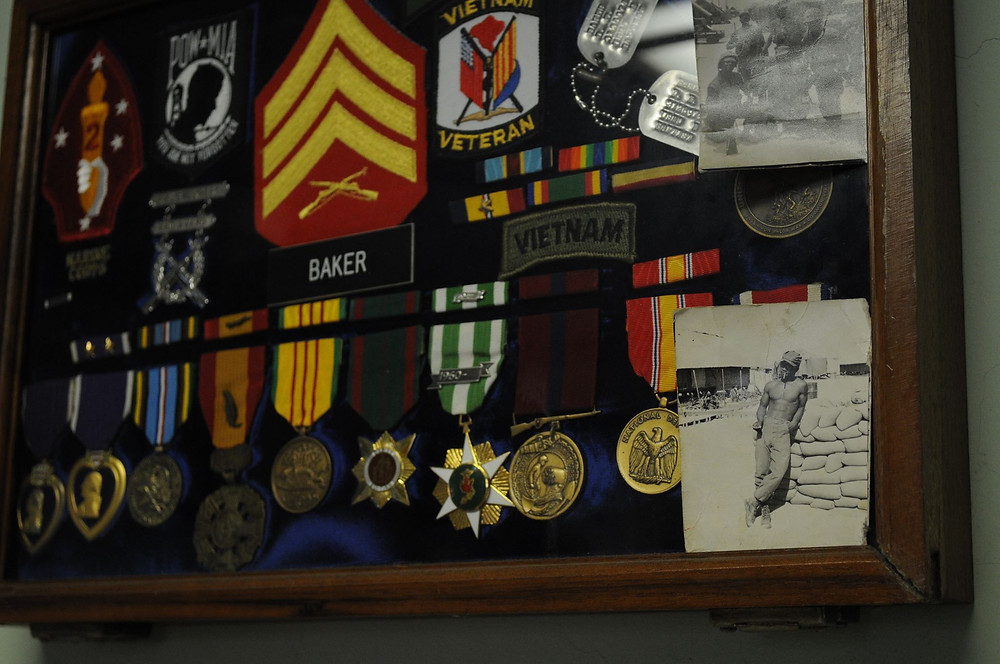Marine Corps shadowbox with military medals, dog tags, patches, and snapshots.