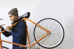 man holding bicycle on shoulder