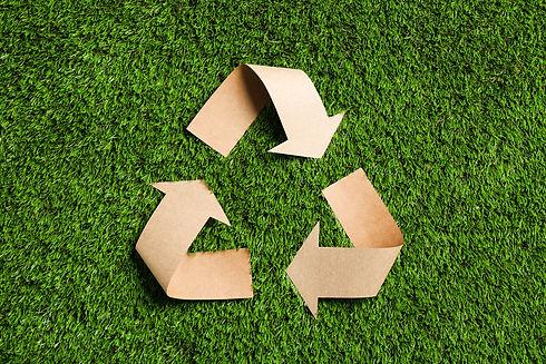 緑の草、上面図のクラフト紙から切り出されたリサイクルシンボル