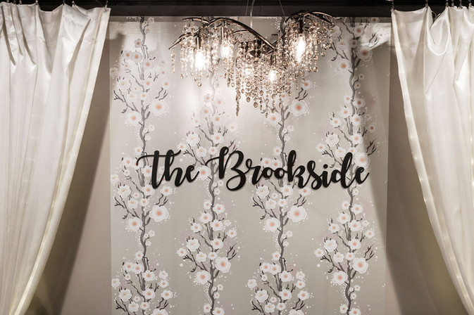 The sateen curtains are backlit by sparkling string lights that flank the peralescant floral wallpaper. An organic shaped crystal chadelier adds sparkle to the room. The Brookside was a custom made metal sign by Bird on the Wire Studio.