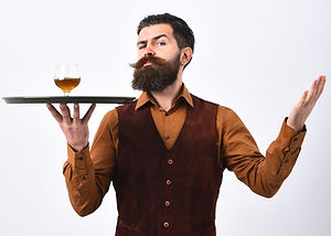 Barman with strict face serves cognac. L