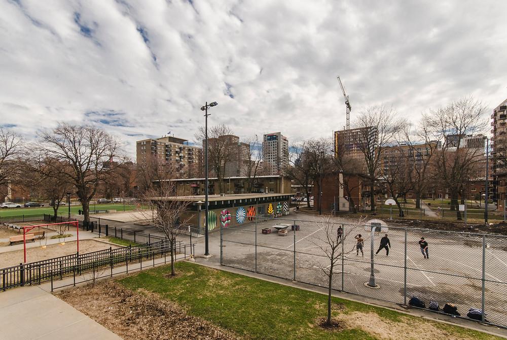 Des aires communes aux Habitations Jeanne-Mance. À l'arrière, les tours de condominium émergent. Crédit: Guillaume Ethier