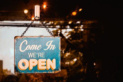 Come In We're Open sign on door of coffe