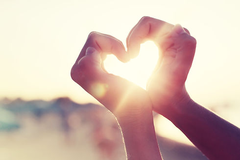 hands in heart shape framing setting sun