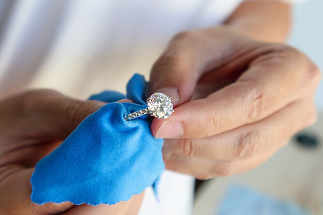 A jeweller cleans a diamond ring