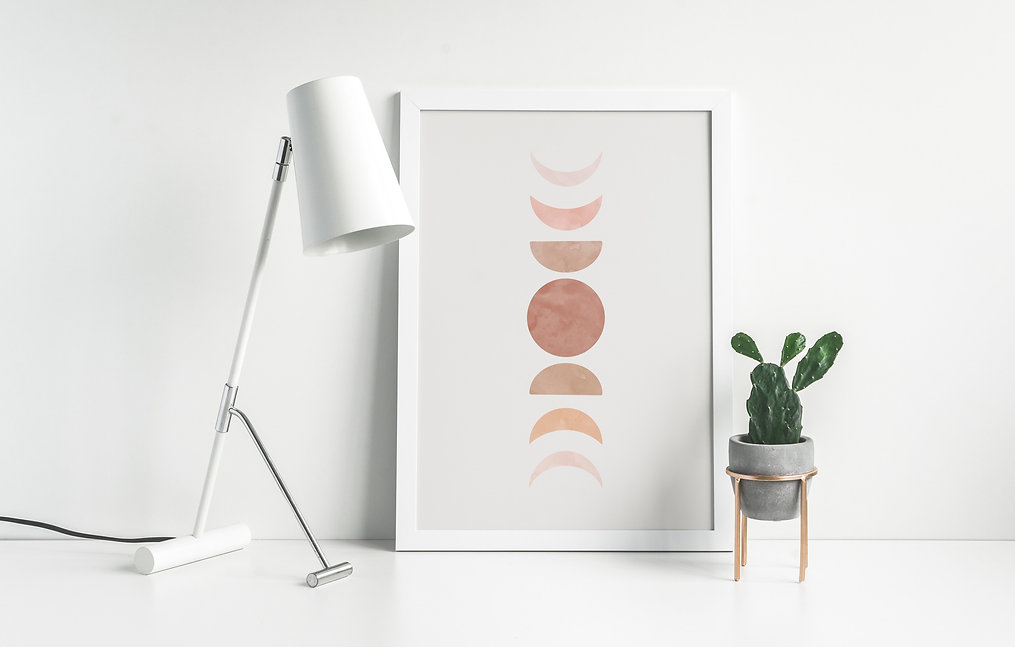 moon phase print in frame sitting on a desk with lamp and succulent