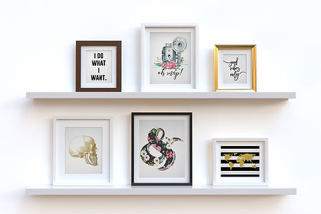 wall prints in frames sitting on shelves