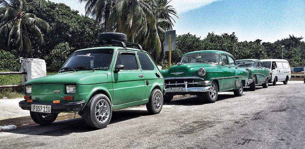 Modified green Fiat 126 in Cuba, with classic Chevrolets