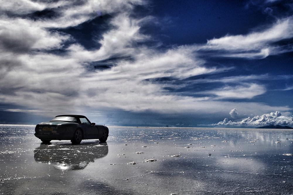 TVR Chimaera on Salar de Uyuni Salt flats in rainy season, Bolivia. Pan American overlanding adventure.