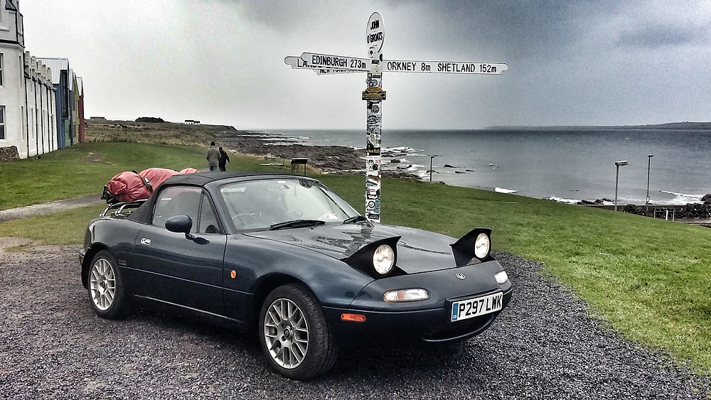 Mazda MX5 Mk1 at John o groats sign NC500 Scottish roadtrip