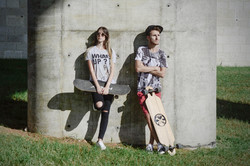 man and woman skaters holding skateboards while leaning on a wall