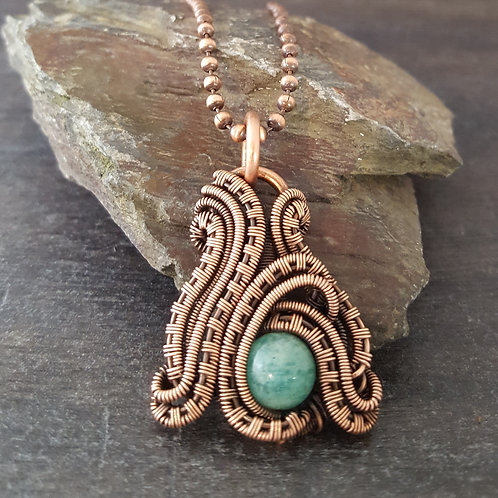 Copper wire woven pendant featuring a turquoise bead.