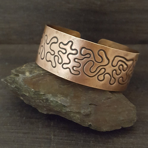 Wide copper cuff bracelet with squiggle design.