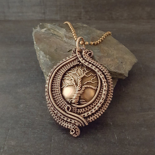 Tree of life over a copper domed disc surrounded with copper wire woven frame pendant.