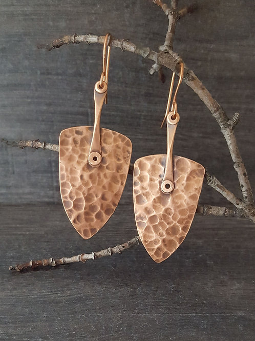 "Hammered ""shield"" shaped copper earrings with rivets."