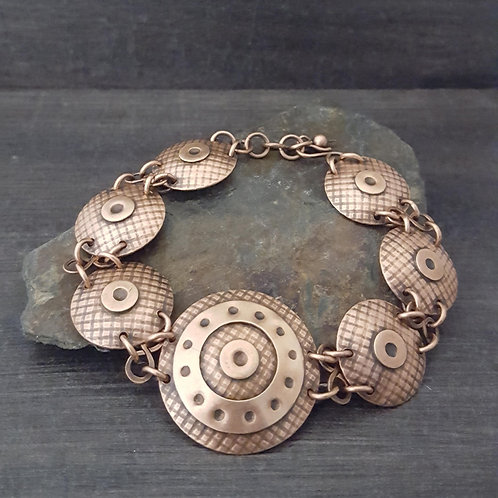 Copper circular domed pattern textured shield design link bracelet.
