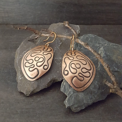 Irregular oval copper earrings with squiggle design.