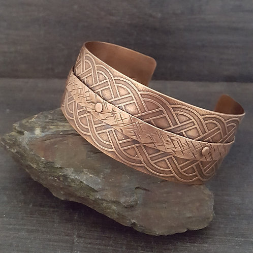 "Celtic design etched onto a copper cuff bracelet with textured ""belt"" riveted on to it."